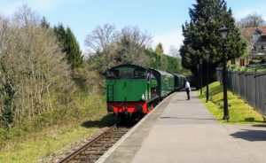Steam train approaches quiet platform with signaller in the countryside