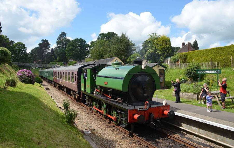 Steam train in countryside approaching station platform