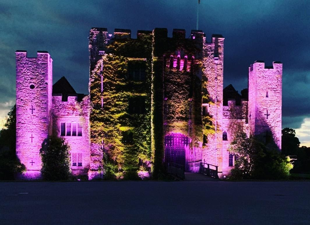 Hever Castle, Kent. Photo shot at night, the castle is lit purple with ivy growing up the front