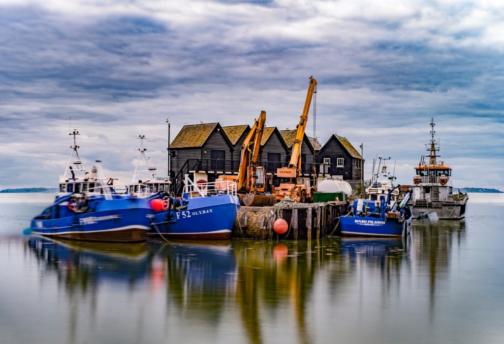 Whitstable, Kent. A view of fishing boats moored at huts with yellow cranes